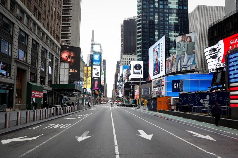FILE PHOTO: People walk through a nearly empty Times Square, during the outbreak of coronavirus disease (COVID-19) in New York