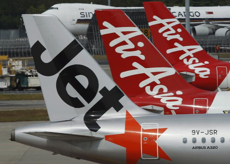 Aircrafts of budget airlines JetStar and AirAsia sit on the tarmac at Singapore's Changi Airport