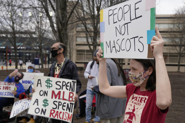 Jolene Adkins, right, protests against racism before a baseball game between the Kansas City Royals and the Cleveland Indians, Monday, April 5, 2021, in Cleveland. (AP Photo/Tony Dejak)
