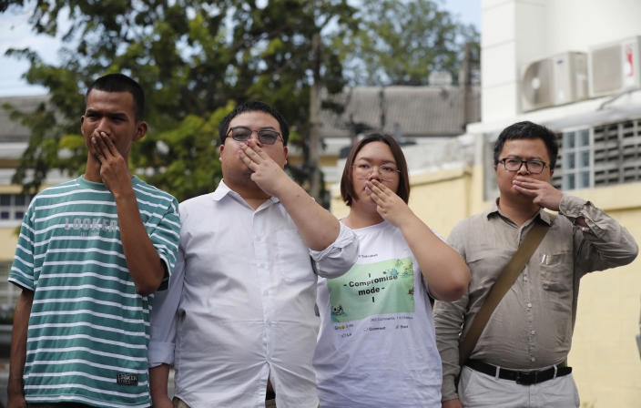 Pro-democracy activists, from left, Panupong Jadnok, Parit Chiwarak, Panusaya Sithijirawattanakul, and Arnon Nampha raise a three-fingers salute, a symbol of resistance at Chana SongKhram police station in Bangkok, Thailand Monday, Nov. 30, 2020. The leaders of the pro-democracy protests reported themselves to the police for the additional charge of violating the lese majeste laws at Chanasongkram Police Station on Monday afternoon. (AP Photo/Sakchai Lalit)