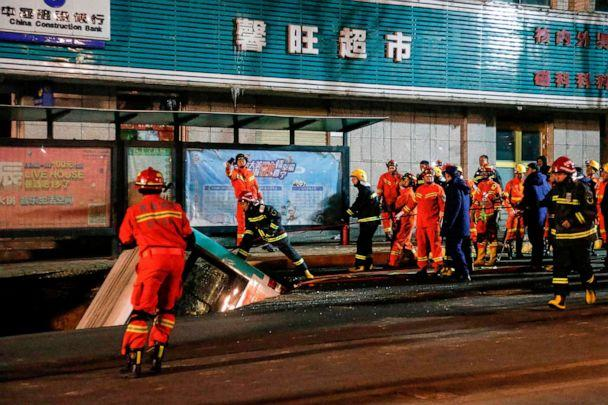 PHOTO: Rescuers prepare to lift a bus after a road collapse in Xining in China. (STR/AFP via Getty Images)