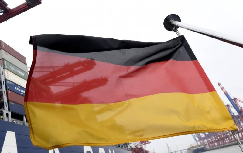 A German flag flutters next to the ships at the loading terminal in the port of Hamburg