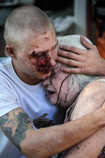 A wounded man hugs an elderly woman after a shelling in the main separatist stronghold in Donetsk, Ukraine on August 23, 2014 (AFP Photo/Dimitar Dilkoff)