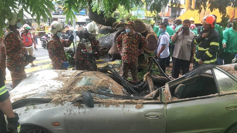 Fire and Rescue Department personnel cutting into the crushed car to extricate the body of the victim. — Pix courtesy of Fire and Rescue Department