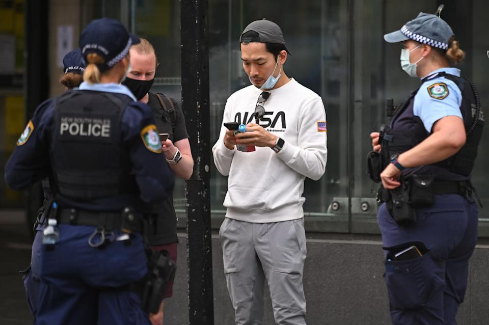 Police officers check ID cards of people walking in the CBD in order to prevent an anti-lockdown protest, during lockdown in Sydney, Australia.