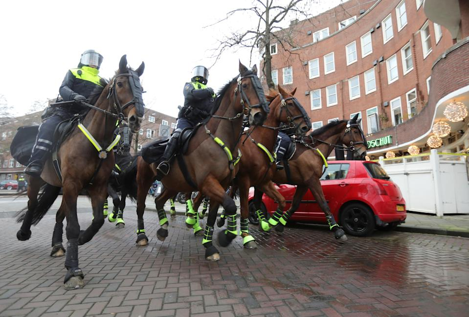 Police officers ride horses during a protest against restrictions in AmsterdamREUTERS