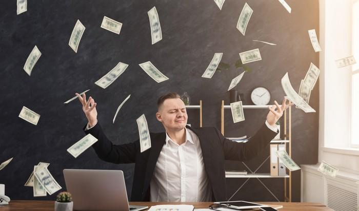 A man in a suit sits at a desk and poses with eyes closed and arms up as cash rains down on him.