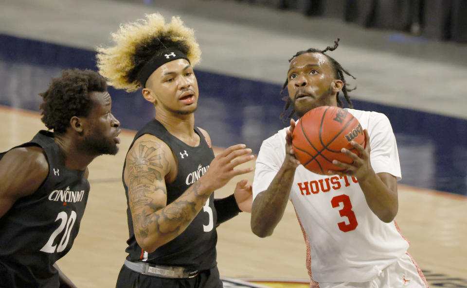 Houston guard DeJon Jarreau, right, drives inside as Cincinnati forward Mamoudou Diarra (20) and Cincinnati guard Mike Saunders, center, defend during the first half of an NCAA college basketball game in the final round of the American Athletic Conference men's tournament Sunday, March 14, 2021, in Fort Worth, Texas. (AP Photo/Ron Jenkins)