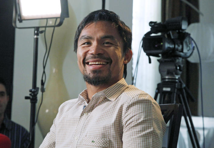 """Manny Pacquiao, world champion boxer and Filipino congressman, smiles during a break while speaking about his views on same-sex marriage, and other subjects, during the taping of a segment of the entertainment TV show """"Extra"""" at his home in Los Angeles on Wednesday, May 16, 2012. Pacquiao says he loves and supports gays and lesbians, even though he does not approve of gay marriage. Pacquiao has been criticized ever since he gave an interview to the examiner.com website in which he opposed President Barack Obama's support for gay marriage. (AP Photo/Reed Saxon)"""