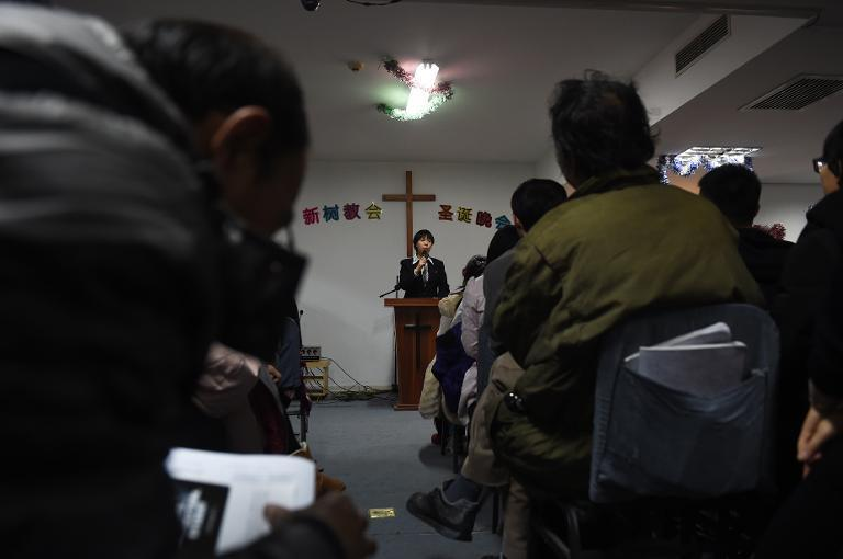 A pastor of an underground church conducts a Christmas Eve service at an apartment in Beijing on December 24, 2014