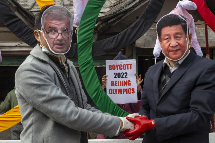 """FILE - In this Feb. 3, 2021, file photo, activists wearing masks of IOC President Thomas Bach, left, and Chinese President Xi Jinping pose in front of the Olympic Rings during a street protest against the holding of the 2022 Beijing Winter Olympics, in Dharmsala, India. Groups alleging human-rights abuses in China are calling for a full boycott of the Beijing Olympics, which is sure to ratchet up pressure on the International Olympic Committee, athletes, sponsors, and sports federations. A coalition of activists representing Uyghurs, Tibetans, residents of Hong Kong and others, issued a statement Monday, May 17, 2021 calling for the """"full boycott,"""" eschewing lesser measures like """"diplomatic boycotts"""" and negotiations with the IOC or China. (AP Photo/Ashwini Bhatia, File)"""