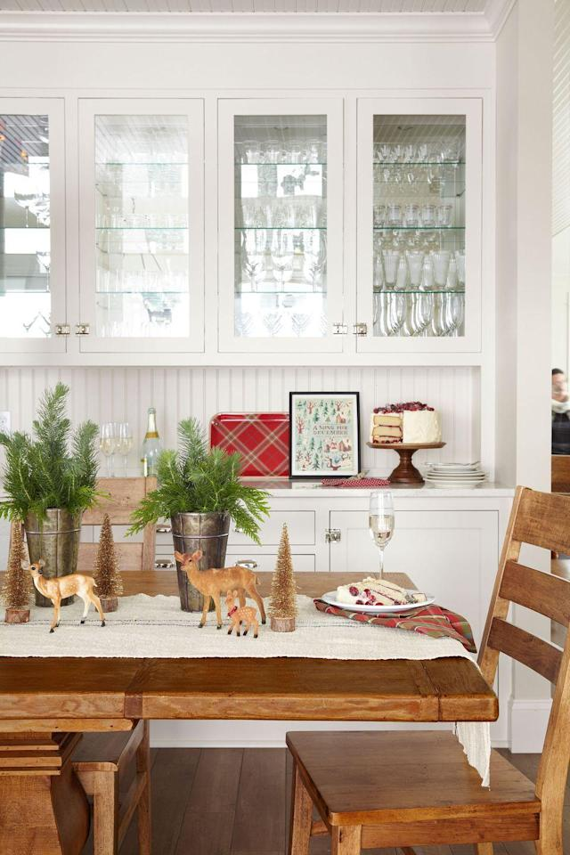 """<p><a href=""""https://www.countryliving.com/home-design/decorating-ideas/g1570/serena-thompson-christmas-decorating-ideas/"""" rel=""""nofollow noopener"""" target=""""_blank"""" data-ylk=""""slk:Serena Thompson"""" class=""""link rapid-noclick-resp"""">Serena Thompson</a>'s attitude about centerpieces: """"Don't overdo it."""" In the dining room, she paired loose sprigs of greenery (in sap buckets, no less) with her collection of toy deer and bottlebrush trees.</p><p><strong><a href=""""https://www.amazon.com/Safari-North-American-Wildlife-Whitetail/dp/B00B3YGIDK/"""" rel=""""nofollow noopener"""" target=""""_blank"""" data-ylk=""""slk:SHOP TOY DEER"""" class=""""link rapid-noclick-resp"""">SHOP TOY DEER</a></strong></p>"""
