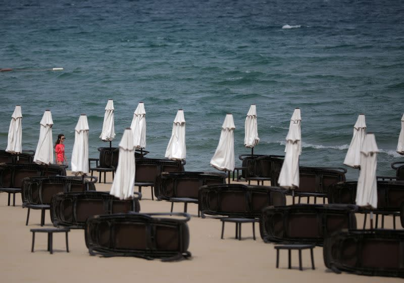 Tourist walks near empty sunbeds at Sunny Beach resort on the Black Sea