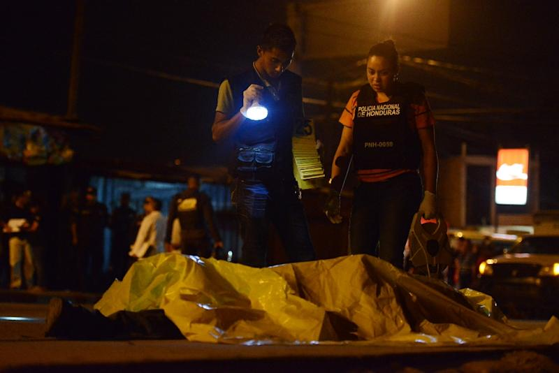 "Police investigate five deaths on May 11, 2015 reportedly related to the non-payment of a ""war tax"" to gangs, in the Carrizal neighborhood north of Tegucigalpa (AFP Photo/Orlando Sierra)"