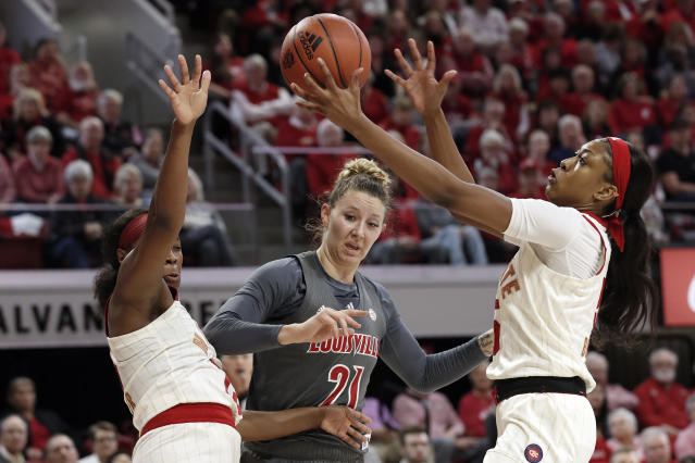 Louisville forward Kylee Shook (21) struggles with North Carolina State guard Grace Hunter, left, and forward Jada Boyd for the ball during the first half of an NCAA college basketball game in Raleigh, N.C., Thursday, Feb. 13, 2020. (AP Photo/Gerry Broome)