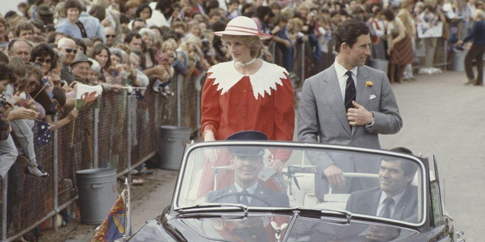 <p>While driving through Memorial Oval in Port Pirie, Australia, Diana wears a Jan Van Velden suit and a hat by John Boyd. Charles smiles at the crown in a gray suit. </p>