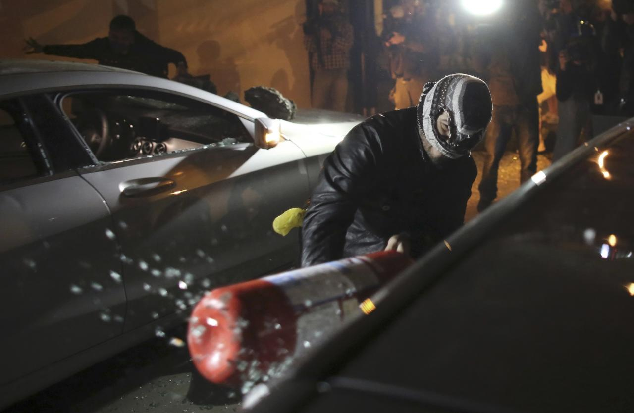 A demonstrator uses a fire extinguisher to smash a car window at a car dealership during a protest against the 2014 World Cup near Marginal Pinheiros in Sao Paulo, June 19, 2014. REUTERS/Nacho Doce (BRAZIL - Tags: SPORT SOCCER WORLD CUP POLITICS CIVIL UNREST)