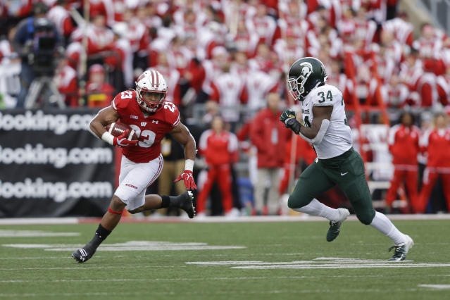 Wisconsin running back Jonathan Taylor (23) makes a reception against Michigan State linebacker Antjuan Simmons (34) during the first half of an NCAA college football game Saturday, Oct. 12, 2019, in Madison, Wis. (AP Photo/Andy Manis)