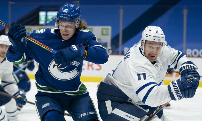 Vancouver Canucks center Adam Gaudette (96) works against Toronto Maple Leafs left wing Zach Hyman (11) during the second period of an NHL hockey game Thursday, March 4, 2021, in Vancouver, British Columbia. (Jonathan Hayward/The Canadian Press via AP)