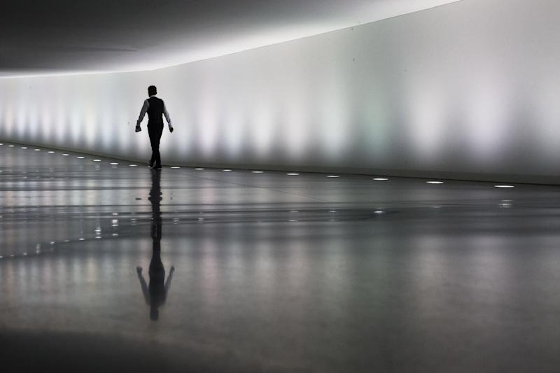 A staff member of the German parliament Bundestag walks through a tunnel between parliament buildings in Berlin, Monday, Sept. 10, 2012. During the first week after the summer break the German parliament will face the budget debate and a decision of Germany's Federal Constitutional Court about the European Stability Mechanism. (AP Photo/Markus Schreiber)