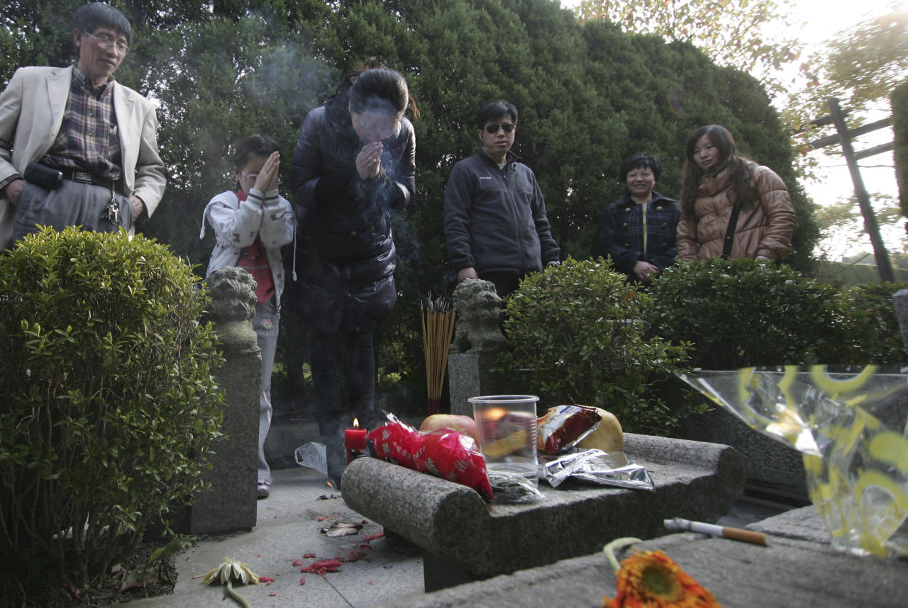People visit their family grave for Qingming Festival in Shanghai, China, Tuesday April. 3, 2012, one day before the actual observance day. The Qingming Festival, a Chinese traditional festival also known as Pure Brightness Festival or Tomb Sweeping Day, falls on April 4 this year, the 15th day from the Spring Equinox. (AP Photo)