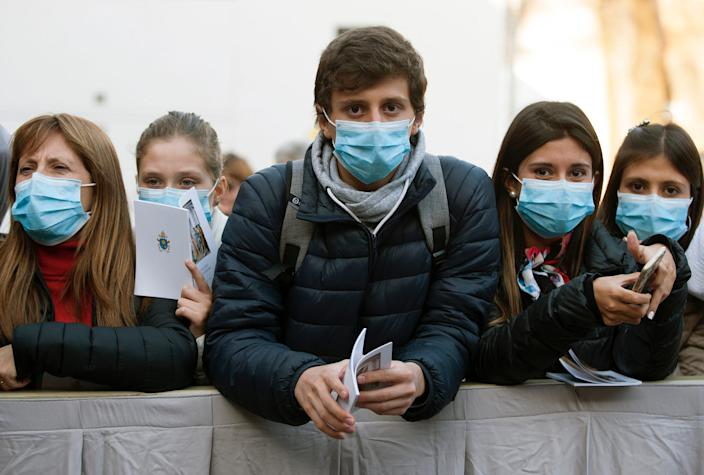 Pilgrims wearing protective face in Vatican City on February 26, 2020.