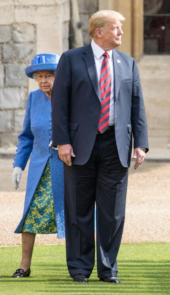 Queen Elizabeth walks with President Trump. (Photo: Getty Images)