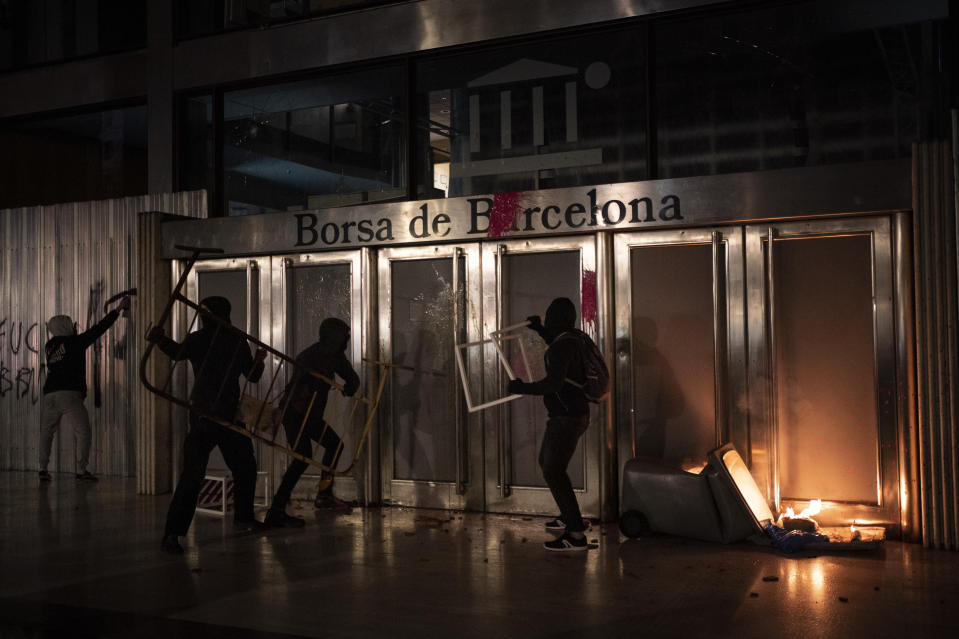 Demonstrators damage the Barcelona Stock Exchange building during a protest condemning the arrest of rap singer Pablo Hasel in Barcelona, Spain, Saturday, Feb. 20, 2021. The imprisonment of Pablo Hasel for inciting terrorism and refusing to pay a fine after having insulted the country's monarch has triggered a social debate and street protests. (AP Photo/Felipe Dana)
