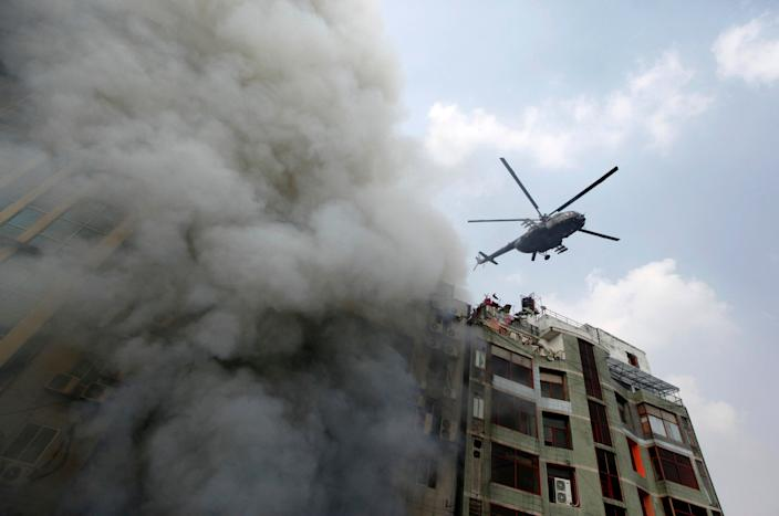 A chopper hovers to evacuate people stuck in a multi-storied office building that caught fire in Dhaka, Bangladesh, March 28, 2019. (AP Photo/Mahmud Hossain Opu )