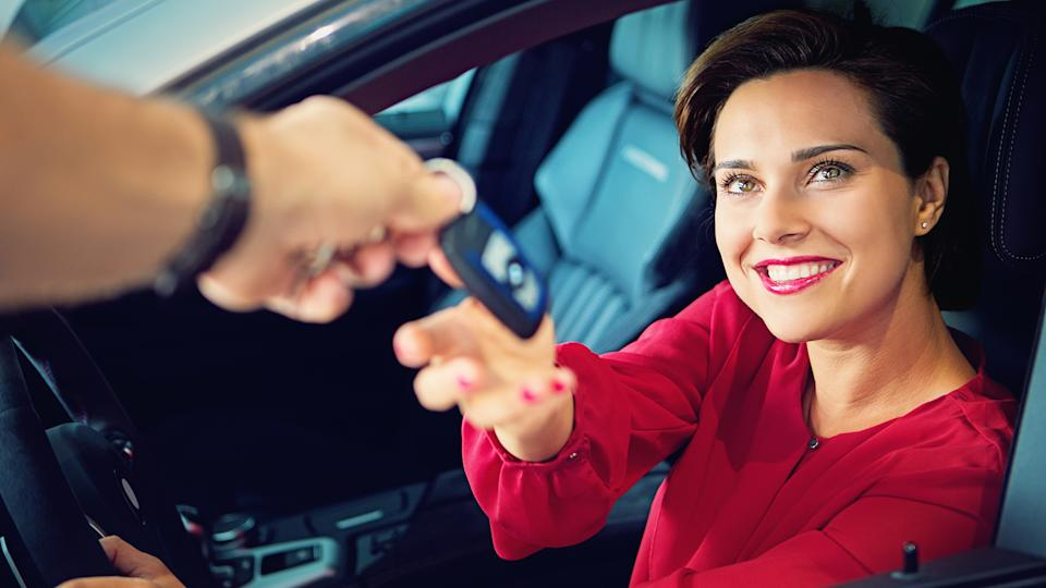 Car dealer is giving car key to a businesswoman.