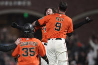 San Francisco Giants' Kevin Gausman, rear, celebrates with Brandon Belt (9) after hitting a sacrifice fly that scored Brandon Crawford (35) during the 11th inning of the team's baseball game against the Atlanta Braves in San Francisco, Friday, Sept. 17, 2021. (AP Photo/Jeff Chiu)