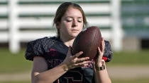 Sam Gordon holds a football, Oct. 20, 2020, in Herriman, Utah. Gordon was the only girl in a tackle football league when she started playing the game at age 9. Now, Gordon hopes she can give girls a chance to play on female-only high school teams through a lawsuit. (AP Photo/Rick Bowmer)