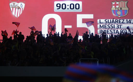 Barcelona fans celebrate at the end of the Copa del Rey final soccer match between Barcelona and Sevilla at the Wanda Metropolitano stadium in Madrid, Spain, Saturday, April 21, 2018. Sevilla lost to Barcelona 5-0. (AP Photo/Paul White)