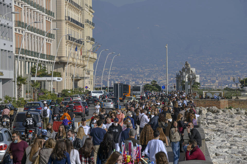 People crowd the Naples waterfront, southern Italy, Sunday, Nov. 8, 2020. In a stark indication of how fast Italy's case numbers are surging, less than two weeks earlier, the total of persons either discharged from hospital or no longer positive for COVID-19 was greater than those currently positive. On Sunday, according to Health Ministry figures, there were some 220,00 more persons currently positive for COVID-19 than discharged or recovered in the entire pandemic. (Alessandro Pone/LaPresse via AP)