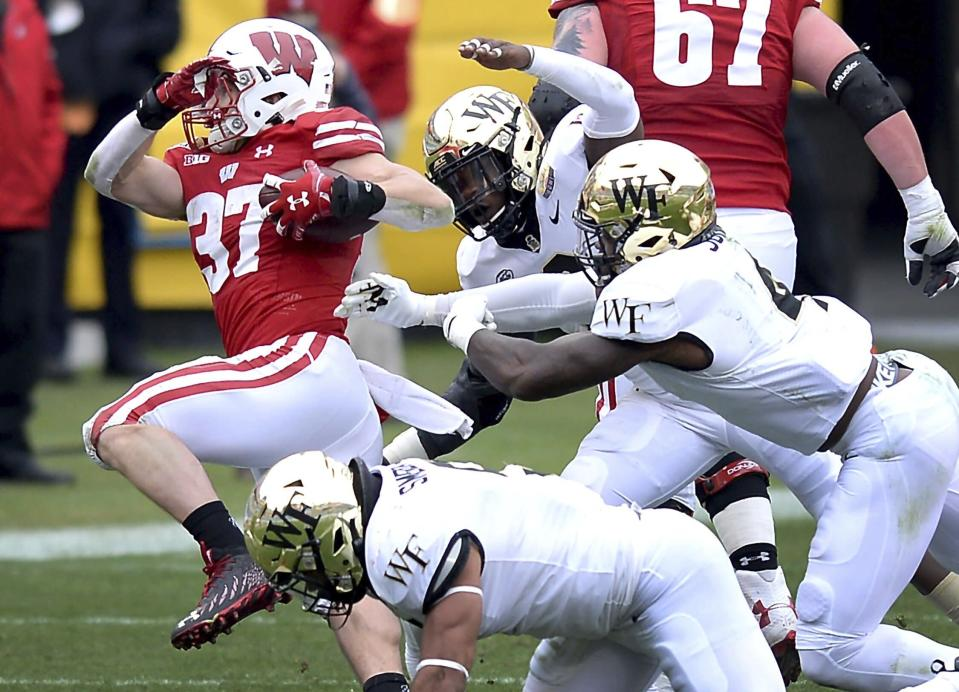 Wake Forest defenders converges on Wisconsin running back Garrett Groshek, left, during the second quarter of the Duke's Mayo Bowl NCAA college football game at Bank of America Stadium in Charlotte, N.C., Wednesday, Dec. 30, 2020. (Jeff Siner/The News & Observer via AP)