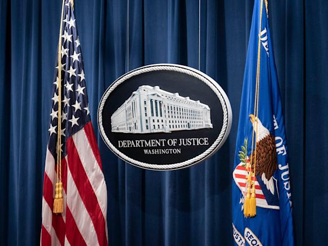 A sign for the Department of Justice is seen ahead of a news conference with Michael Sherwin, acting US attorney for the District of Columbia, and Steven D'Antuono, head of the Federal Bureau of Investigation (FBI) Washington field office, at the US Department of Justice in Washington, DC, on 12 January 2021 ((POOL/AFP via Getty Images))