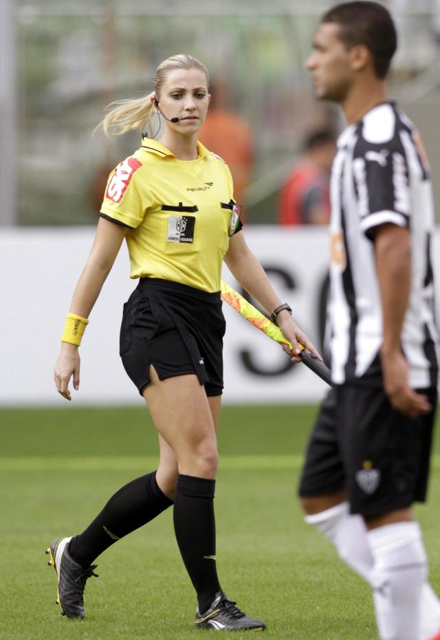 Brazil's referee assistant Fernanda Colombo Uliana walks next to an Atletico Mineiro player before the Brazilian championship soccer match between Atletico Mineiro and Cruzeiro in Belo Horizonte May 11, 2014. Uliana has just been granted FIFA official status by the refereeing committee of the Brazilian Football Confederation. REUTERS/Washington Alves (BRAZIL - Tags: SPORT SOCCER)