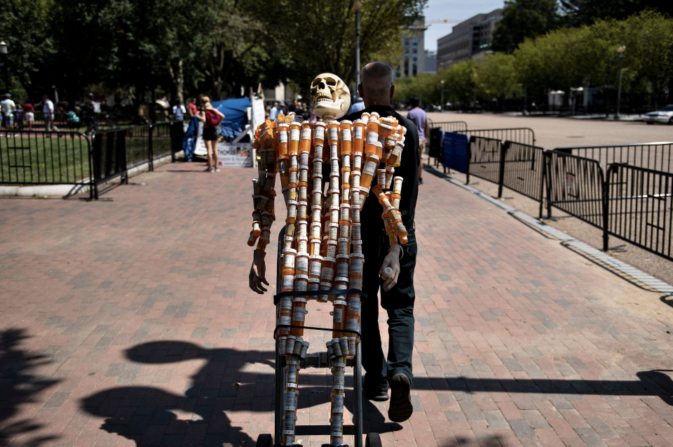 Frank Huntley, who struggled with addiction, walks with Pill Man, a skeleton made from his oxycontin and methadone prescription bottles, along Pennsylvania Avenue August 30, 2019, in Washington, DC. (Photo: BRENDAN SMIALOWSKI/AFP/Getty Images)