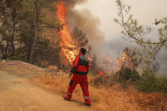 Firefighters work in the smoke-engulfed Mazi area as wildfires rolled down the hill toward the seashore, forcing people to be evacuated, in Bodrum, Mugla, Turkey, Sunday, Aug. 1, 2021. More than 100 wildfires have been brought under control in Turkey, according to officials. The forestry minister tweeted that five fires are continuing in the tourist destinations of Antalya and Mugla. (AP Photo/Emre Tazegul)