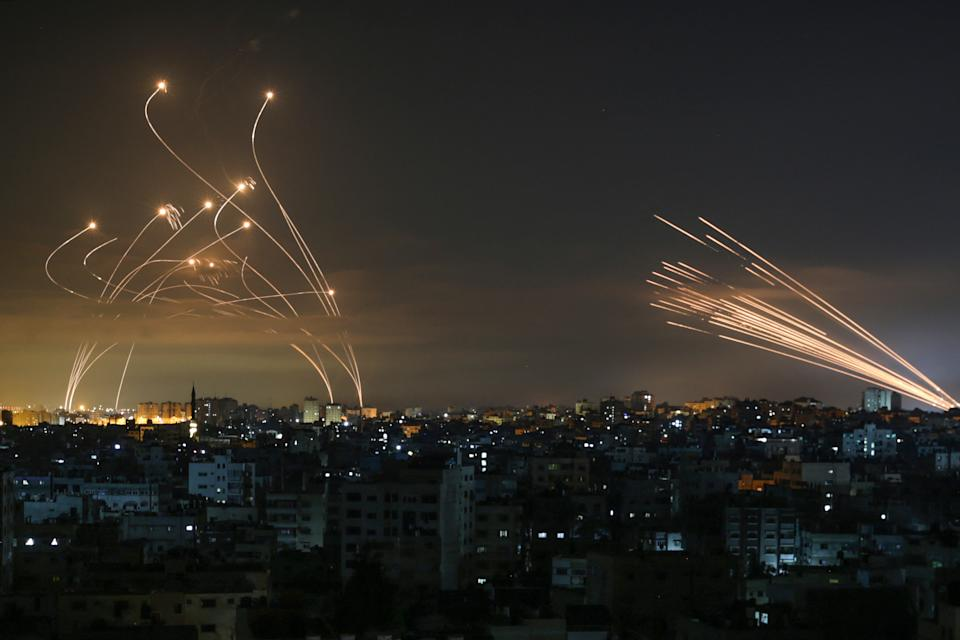 Rockets are seen in the night sky fired towards Israel from Beit Lahia in the northern Gaza Strip on May 14, 2021. - Israel bombarded Gaza with artillery and air strikes on Friday, May 14, in response to a new barrage of rocket fire from the Hamas-run enclave, but stopped short of a ground offensive in the conflict that has now claimed more than 100 Palestinian lives. As the violence intensified, Israel said it was carrying out an attack