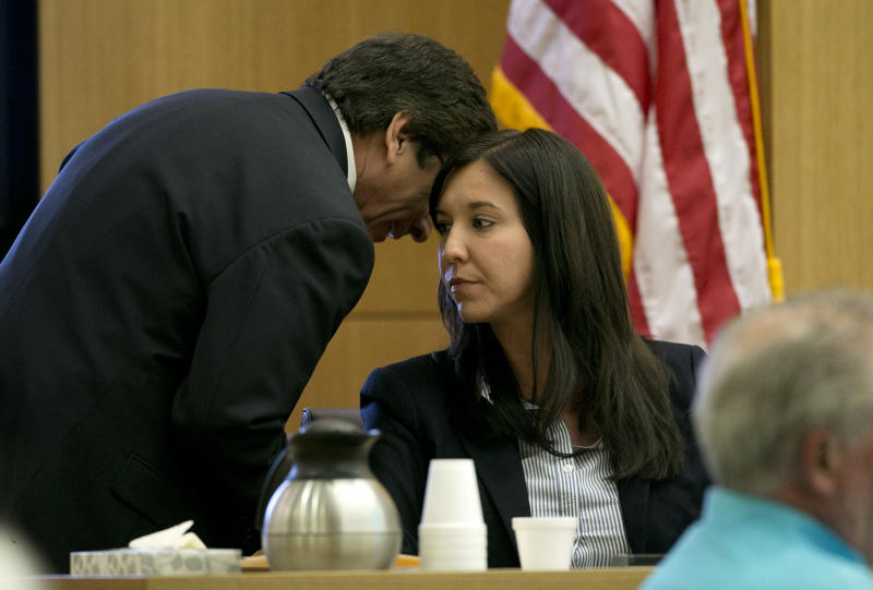 Prosecutor Juan Martinez whispers ion the ear of Dr. Janeen DeMarte an expert witness for the prosecution during the Jodi Arias trial at Maricopa County Superior Court in Phoenix on Tuesday, April 16, 2013. Defense attorneys rested their case Tuesday after about 2 1/2 months of testimony aimed at portraying Arias as a domestic violence victim who fought for her life the day she killed her one-time boyfriend.  (AP Photo/The Arizona Republic, David Wallace, Pool)