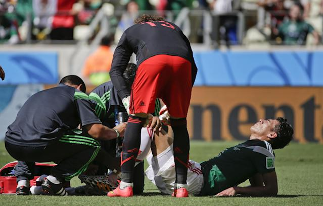 Mexico's Hector Moreno grimaces while being looked after by medical personnel during the World Cup round of 16 soccer match between the Netherlands and Mexico at the Arena Castelao in Fortaleza, Brazil, Sunday, June 29, 2014. (AP Photo/Felipe Dana)