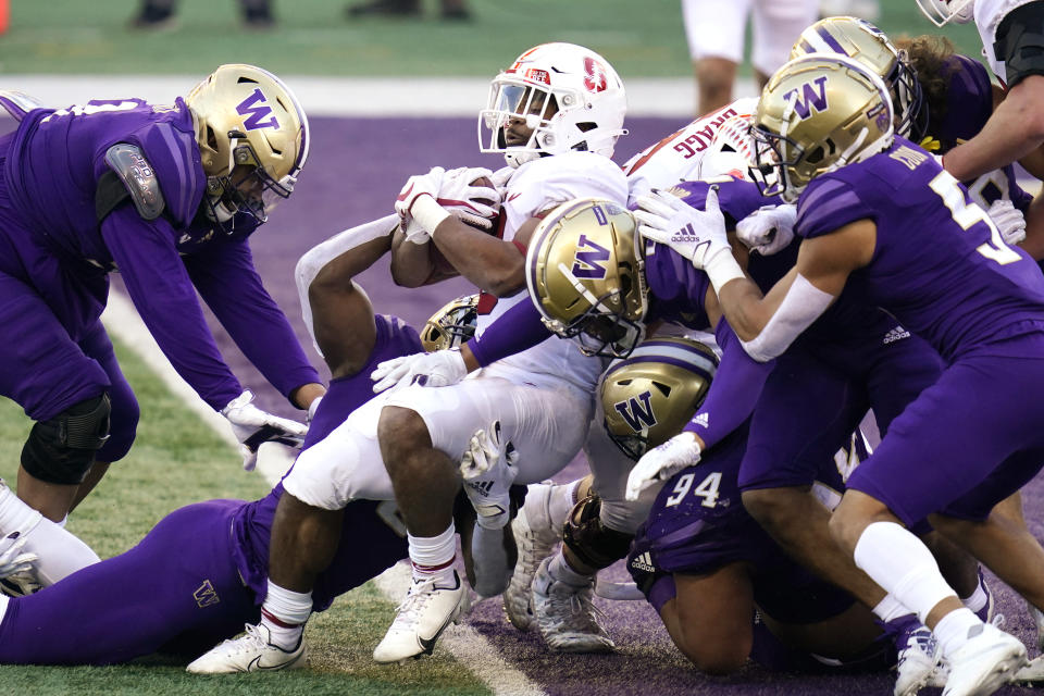Stanford running back Nathaniel Peat, center, pushes into the end zone on a 3-yard touchdown run against Washington in the first half of an NCAA college football game Saturday, Dec. 5, 2020, in Seattle. (AP Photo/Elaine Thompson)