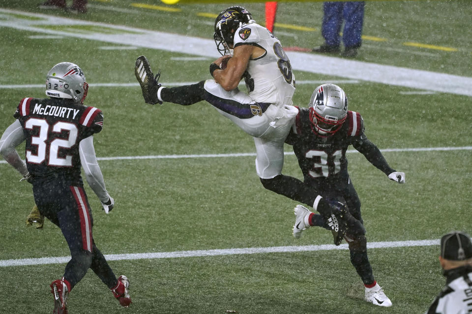 Baltimore Ravens wide receiver Willie Snead IV, center, catches a touchdown pass between New England Patriots defensive backs Devin McCourty, left, and Jonathan Jones, right, in the second half of an NFL football game, Sunday, Nov. 15, 2020, in Foxborough, Mass. (AP Photo/Charles Krupa)