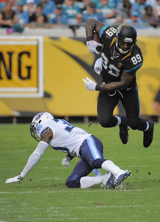 Jacksonville Jaguars tight end Marcedes Lewis (89) leaps over Tennessee Titans cornerback Jason McCourty after a reception during the second half of an NFL football game in Jacksonville, Fla., Sunday, Dec. 22, 2013. Tennessee defeated Jacksonville 20-16. (AP Photo/Stephen Morton)