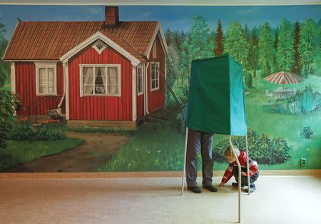 A man and a boy stand at a booth in front of a mural at a polling station during general elections in Stockholm in this September 19, 2010 file photo. REUTERS/Soren Andersson/TT News Agency/Files