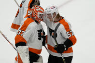 Philadelphia Flyers goaltender Brian Elliott (37) and right wing Wade Allison (57) celebrate after during an NHL hockey game against the Washington Capitals, Friday, May 7, 2021, in Washington. The Flyers won 4-2. (AP Photo/Alex Brandon)