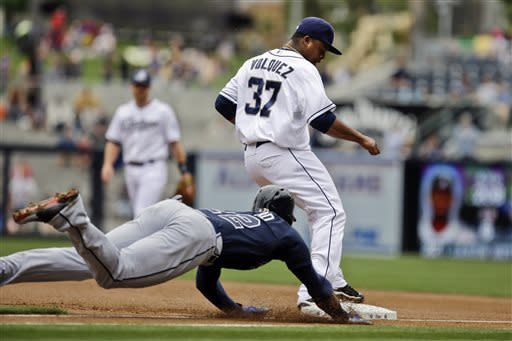 San Diego Padres pitcher Edinson Volquez beats the diving slide of Atlanta Braves' Jason Heyward to first base for an out during the first inning of a baseball game Wednesday, June 12, 2013, in San Diego. (AP Photo/ Lenny Ignelzi)