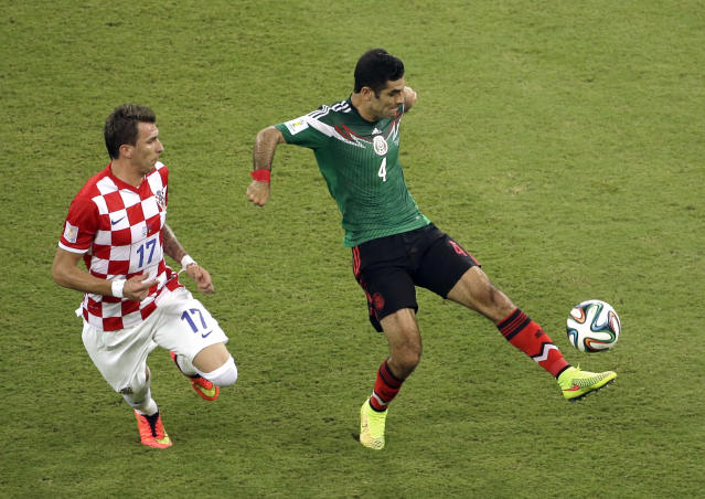 Mexico's Rafael Marquez controls the ball against Croatia's Mario Mandzukic during the group A World Cup soccer match between Croatia and Mexico at the Arena Pernambuco in Recife, Brazil, Monday, June 23, 2014. (AP Photo/Hassan Ammar)