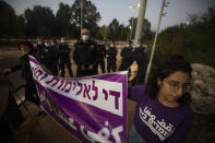 """Israeli police officers stand guard as protesters hold signs and chant slogans during a demonstration against violence near the house of Public Security Minister Omer Barlev in the central Israeli town of Kokhav Ya'ir, Saturday, Sept. 25, 2021. Arab citizens of Israel are seeking to raise awareness about the spiraling rate of violent crime in their communities under the hashtag """"Arab lives matter,"""" but unlike a similar campaign in the United States, they are calling for more policing, not less. Hebrew reads: """"enough violence and crime.""""(AP Photo/Sebastian Scheiner)"""
